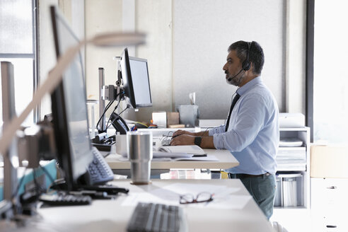 Businessman with headset using computers at sit-stand desk in office - HEROF16823