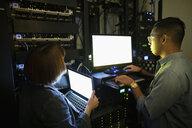 IT technicians using laptops in dark server room - HEROF16871