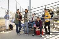 Portrait confident Latinx family at bleachers during baseball game - HEROF16910