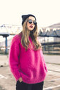 Portrait of fashionable young woman wearing sunglasses, cap and pink knit pullover - ACPF00428