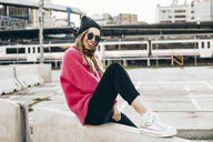 Portrait of fashionable young woman wearing sunglasses, cap and pink knit pullover - ACPF00431