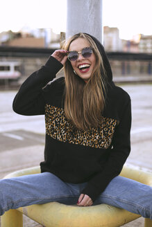 Portrait of fashionable young woman wearing sunglasses and black hooded jacket with pattern - ACPF00434