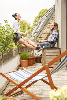Young couple sitting on their balcony in summer, talking and using laptop - PESF01104