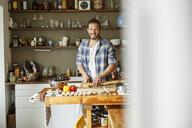Young man preparing food at home, slicing bread - PESF01107