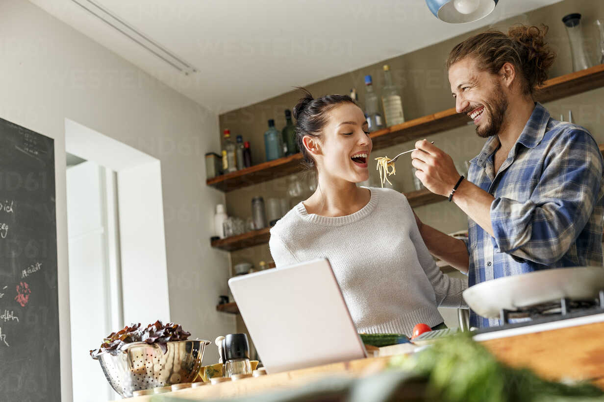 Young couple preparing spaghetti together, using online recipe - PESF01125 - Peter Scholl/Westend61
