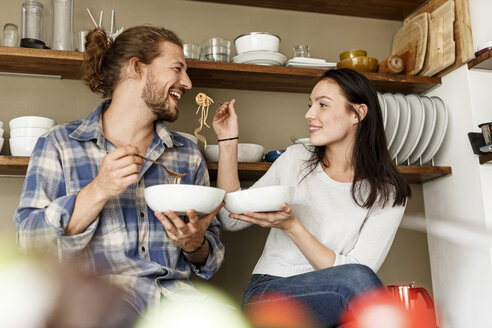 Happy couple sitting in kitchen, eating spaghetti - PESF01128