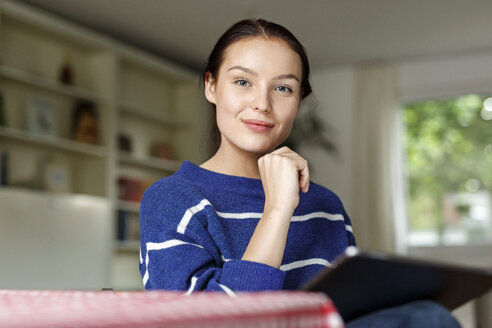 Young woman sitting at home, using digital tablet - PESF01134