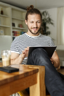Young man with a bun sitting at home, using digital tablet - PESF01143