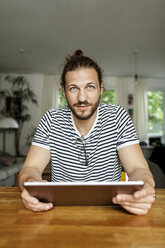 Young man with a bun sitting at home, using digital tablet - PESF01149
