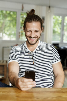 Young man with a bun sitting at home, using smartphone - PESF01152