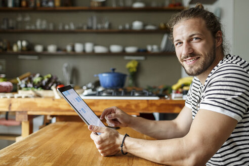 Young man with a bun sitting at home, using digital tablet - PESF01155