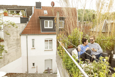 Young couple relaxing on their balcony, sitting on couch - PESF01158