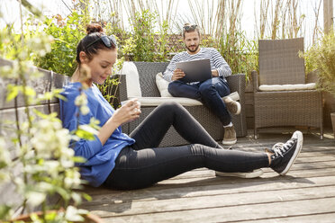 Young couple relaxing on their balcony, man sitting on couch, using laptop - PESF01164