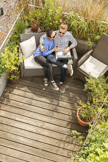Young couple relaxing on their balcony, sitting on couch, using laptop - PESF01167