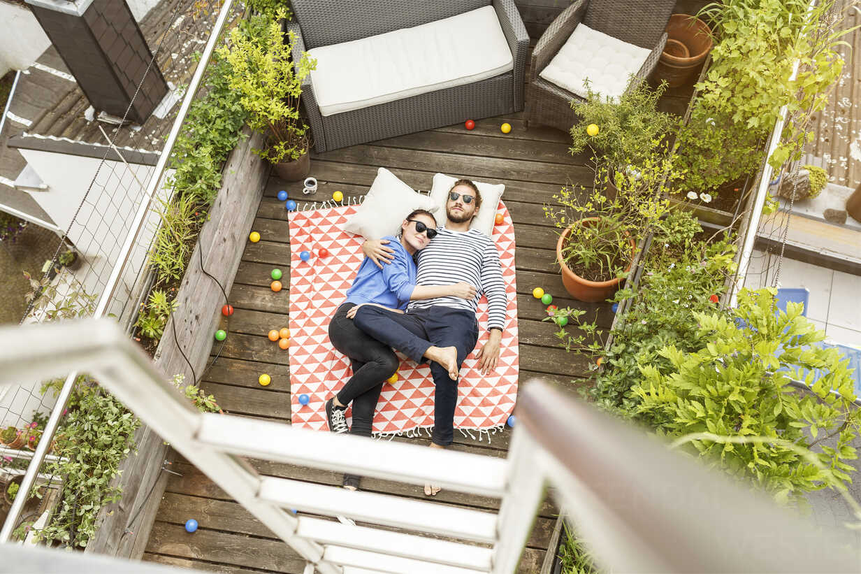 Young couple relaxing on their balcony, lying on blanket with arms around - PESF01173 - Peter Scholl/Westend61