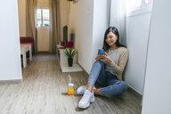 Young woman sitting on floor, using smartphone - KIJF02267