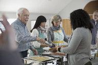 Senior man serving food at soup kitchen community dinner - HEROF17012