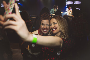 Smiling, confident millennial women friends taking selfie with camera phone at music concert - HEROF17021