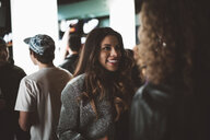 Smiling young female millennial talking with friends in bar - HEROF17027