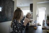 Sisters in pajamas eating breakfast at dining table - HEROF17072