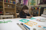 Preschool girl with stencils making art and craft project in classroom - HEROF17171