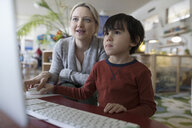 Preschool teacher and boy student at computer - HEROF17186
