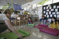 Preschool teacher and students unrolling yoga mats in classroom - HEROF17198