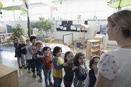 Preschool students lining up for teacher in classroom - HEROF17225