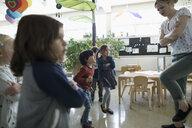 Preschool teacher and students playing, dancing in classroom - HEROF17228