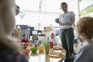 Preschool teacher talking to students during snack time - HEROF17243