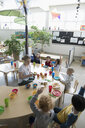 Preschool teacher and students eating during snack time in classroom - HEROF17246