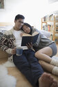 Affectionate couple cuddling, reading book and drinking coffee in morning bedroom - HEROF17354