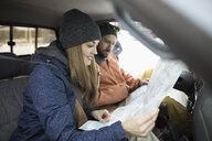 Adventurous couple checking map in truck - HEROF17366