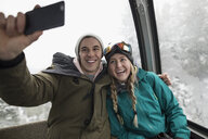 Affectionate, enthusiastic skier couple riding gondola, taking selfie with smart phone - HEROF17369