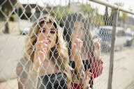 Portrait confident, tough Latinx young women friends behind fence - HEROF17384
