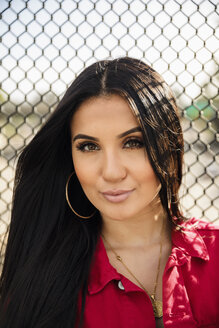 Portrait confident Latinx young woman against fence - HEROF17408