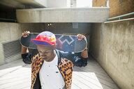 Cool young man holding skateboard at urban parking garage entrance - HEROF17537