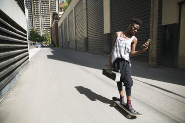 Cool young woman skateboarding with boom box and texting in urban alley - HEROF17546