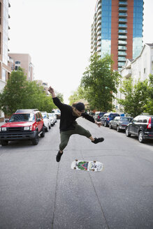Cool young man flipping skateboard in urban street - HEROF17585