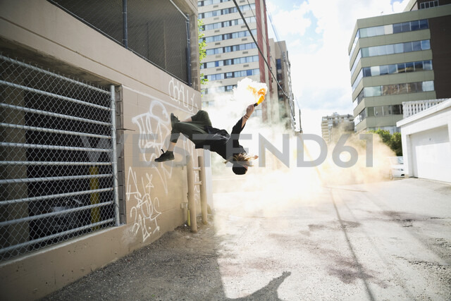 Cool young man doing parkour backflipping with powder cannon in urban alley - HEROF17588 - Hero Images/Westend61