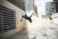 Cool young man doing parkour backflipping with powder cannon in urban alley - HEROF17588