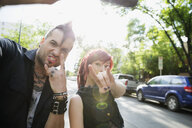 Cool couple with attitude taking selfie gesturing horn sign in street - HEROF17606
