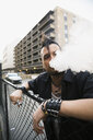 Cool man with mohawk smoking electronic cigarette at urban fence - HEROF17612
