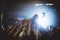 Woman with camera phone crowdsurfing at music concert in nightclub - HEROF17732