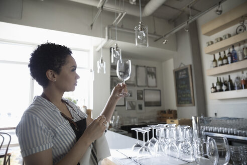 Young woman small business owner drying wine glasses in bar - HEROF17735