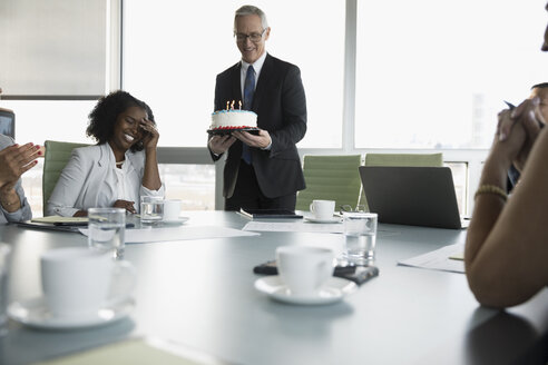 Businessman serving birthday cake to surprised businesswoman in conference room - HEROF17801