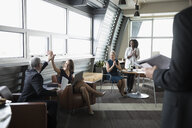 Business people celebrating, high-fiving in business lounge - HEROF17813