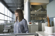 Ambitious, confident businesswoman looking away in office cubicle - HEROF17858
