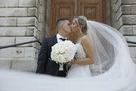 Bride in long veil and groom kissing outside church - HEROF17876