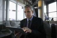 Focused businessman using digital tablet in office cubicle - HEROF17996
